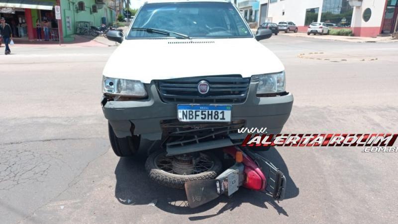Moto vai parar embaixo de carro após colisão no Centro de Rolim de Moura